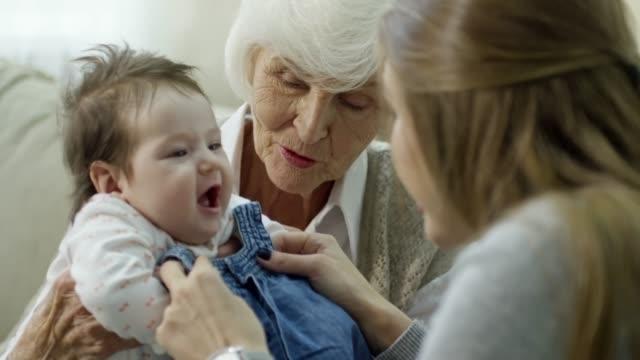 vídeos y material grabado en eventos de stock de madre tratando de nuevo vestido de bebé feliz - nuevo bebé