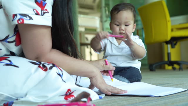 mother trying on to teach her baby boy draw a picture - vídeo