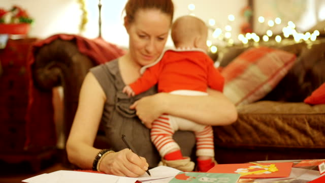 vídeos de stock e filmes b-roll de mother trying to write out christmas cards with baby - christmas card