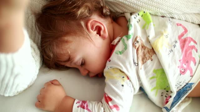 madre che usa il cellulare accanto al bambino addormentato. genitore sdraiato sul divano a digitare su smartphone mentre il bambino fa un pisolino - sonnecchiare video stock e b–roll