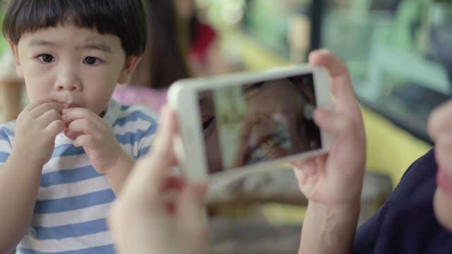 vídeos de stock e filmes b-roll de mother using mobile phone shoots a photo with baby boy - fotografar