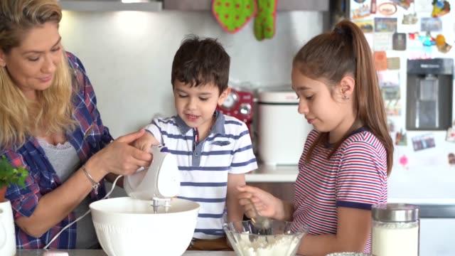 vidéos et rushes de mère 4k utilisant le masque protecteur faisant des petits gâteaux délicieux avec ses enfants isolement à la maison pour le virus - batteur électrique
