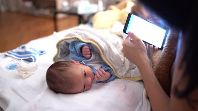 vidéos et rushes de mère à l'aide d'un téléphone intelligent à côté de bébé - 0 11 mois