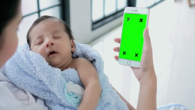 mother using smartphone (green screen)while holding her child. - dolly shot video stock e b–roll