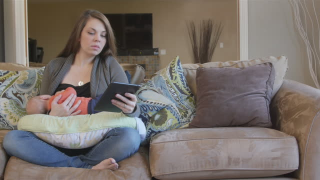 Mother using tablet computer while breastfeeding video