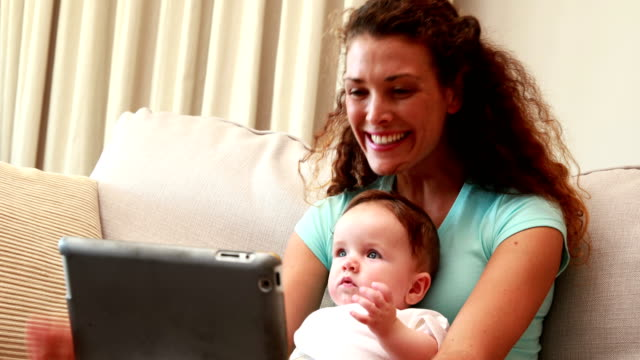 Mother using tablet pc for video chat with baby son on her lap video