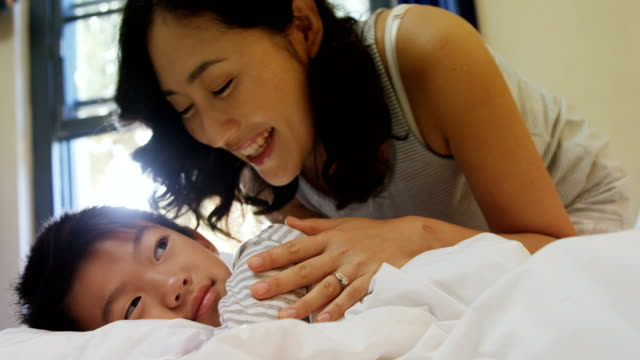 Mother waking up her son in bedroom 4k video