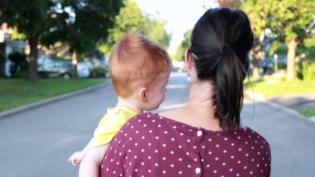 mor promenader med baby boy i armar - walking home sunset street bildbanksvideor och videomaterial från bakom kulisserna