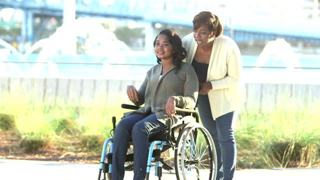 Mother walking with teenage daughter in wheelchair A 15 year old teenage girl sitting in a wheelchair, spending time outdoors with her mother,, at a city park on a sunny day. sociology stock videos & royalty-free footage