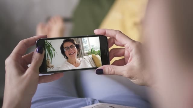 mother waving and blowing kiss to her daughter through smart phone video call - video call video stock e b–roll