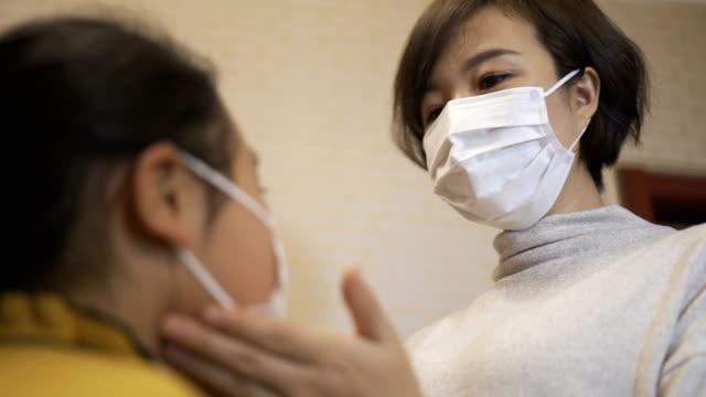 anne kızı için tıbbi yüz maskesi giyiyor - maske stok videoları ve detay görüntü çekimi