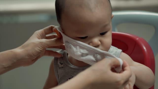 Mère utilisant le masque médical de visage pour son fils - Vidéo
