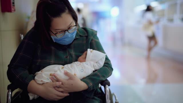 vidéos et rushes de la mère portant des masques de virus de prévention admirant le bébé nouveau-né dormant à l'hôpital - admiration
