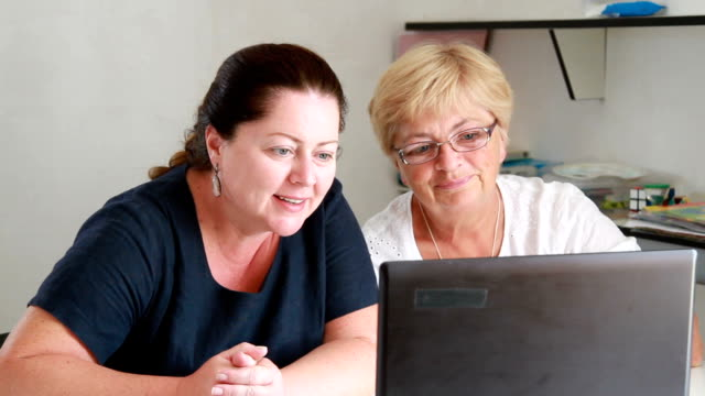 mother with an adult daughter talking on the Internet on a laptop video