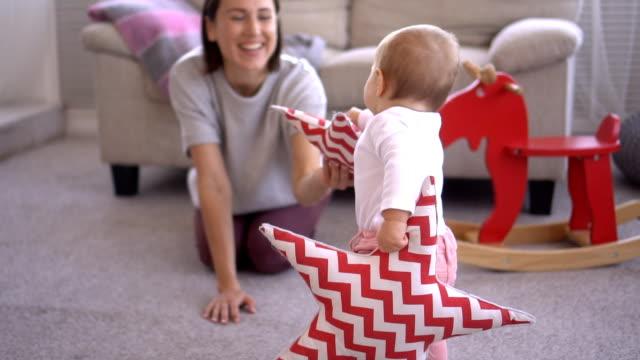 stockvideo's en b-roll-footage met moeder met babymeisje uitvoering stervorm kussen - baby toy