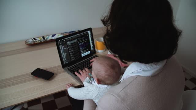 mamma med baby i varv multitasking med telefon och dator - working from home bildbanksvideor och videomaterial från bakom kulisserna