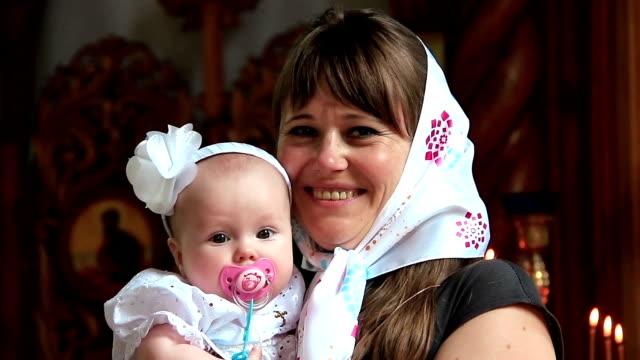 正教会で赤ちゃんを持つ母 - 洗礼点の映像素材/bロール
