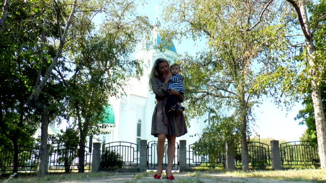mother with baby on a background of church - christening stock videos and b-roll footage