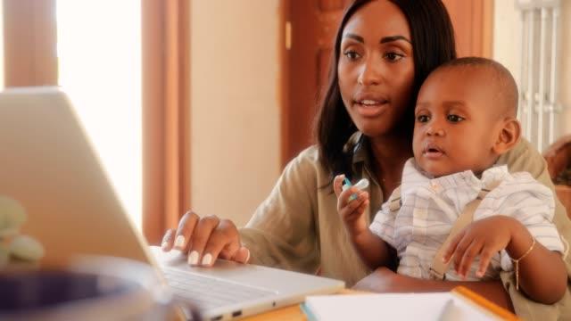 mor med baby son använder bärbar dator och arbeta hemifrån - working from home bildbanksvideor och videomaterial från bakom kulisserna