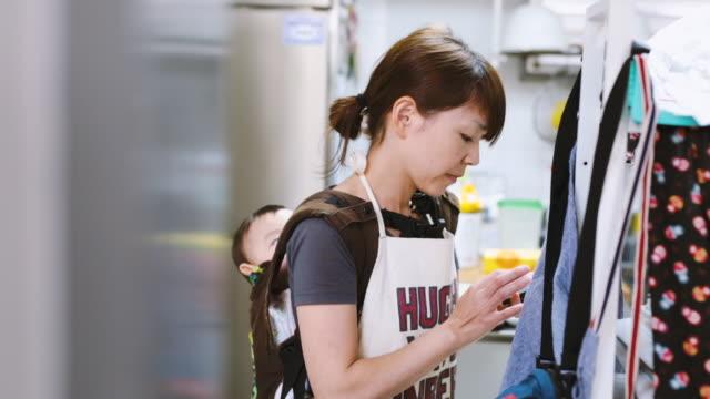 スマートフォンを使った赤ちゃんを持つ母親 - 日本人のみ点の映像素材/bロール