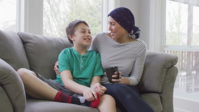Mother With Cancer Sitting with Her Son A recovering cancer patient wearing a scarf sits on the couch with her son. She is holding a mug in her hand while she has her arm around her son cancer patient stock videos & royalty-free footage