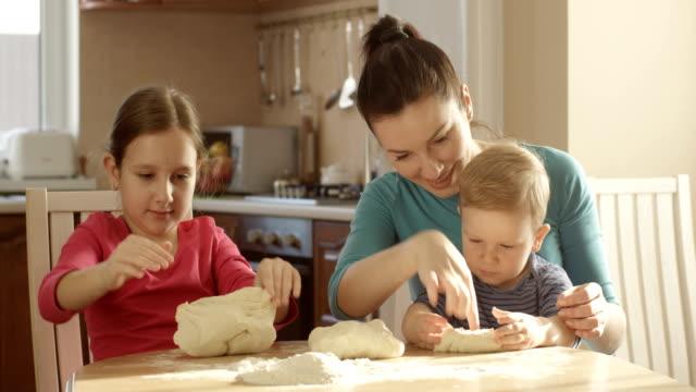 Mutter mit Kindern Kneten von Teig für Kuchen in der Küche am Tisch – Video