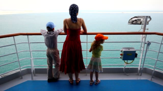 Mother with children stands on deck of cruise ship video