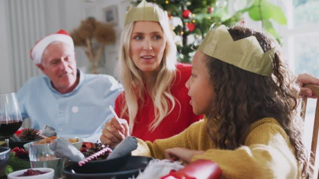 madre con figlia e nonno a tavola a leggere le battute del cracker di natale durante il pasto a casa - pranzo di natale video stock e b–roll