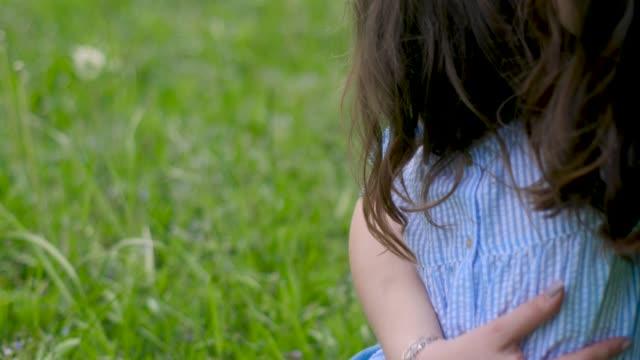 mère avec la fille dans des robes bleues s'asseoir sur un champ vert - Vidéo
