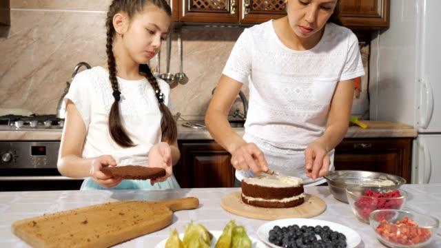 kızı ile anne bıçak kullanarak çikolata sünger kek üzerinde beyaz muhallebi smear. - muhallebi stok videoları ve detay görüntü çekimi