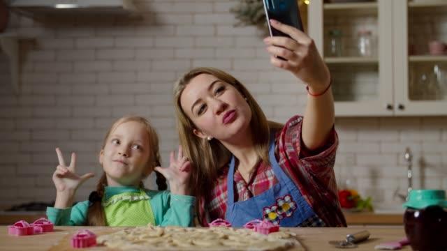 mor med dotter tar selfie skjuten i köket - videor med baka bildbanksvideor och videomaterial från bakom kulisserna