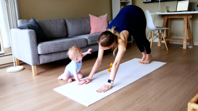 mother with her baby performing yoga 4k - edificio residenziale video stock e b–roll