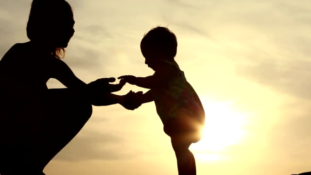mother with her child on the beach at evening video