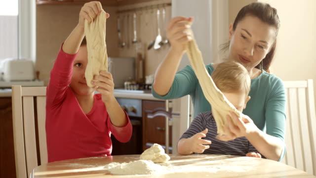 Mutter mit ihren Kindern Spaß kneten Teig und Kochen Kuchen – Video