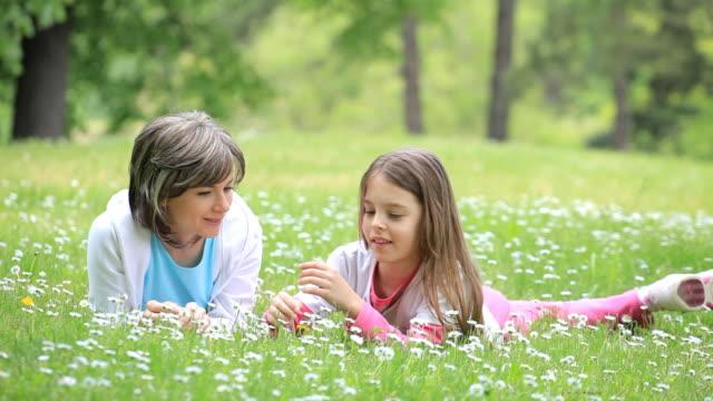 Madre con su hija descansando en green park. - vídeo