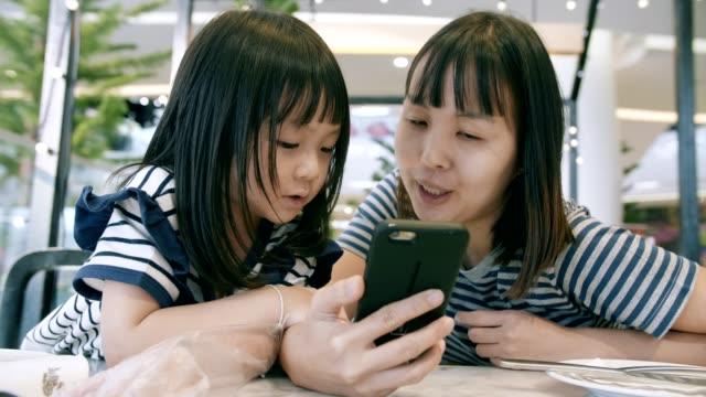 mamma med sin dotter med en smartphone - enbarnsfamilj bildbanksvideor och videomaterial från bakom kulisserna