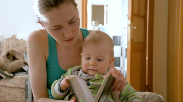 Mother with her son flipping through scrapbook video