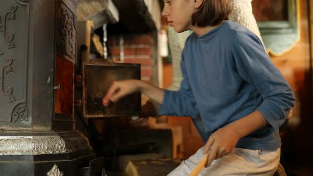 oğluyla birlikte ateşle şöminenin yanında olan anne - şömine odunu stok videoları ve detay görüntü çekimi
