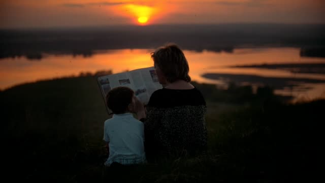Mother with her son reading a book on the hill swatting at mosquitoes at summer sunset video