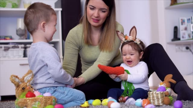 Bидео Mother with kids sitting on the floor and playing with Easter egg