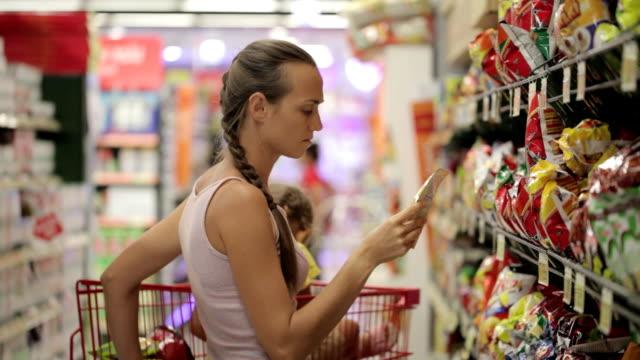 mutter mit töchterchen auswahl snacks süßigkeiten abschnitt im supermarkt - etikett stock-videos und b-roll-filmmaterial