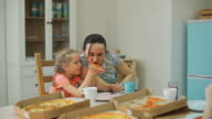 istock Mother with Little Daughter Eating Pizza at Home 1222188731