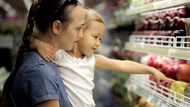 Mother with little daughter makes purchases in the supermarket video