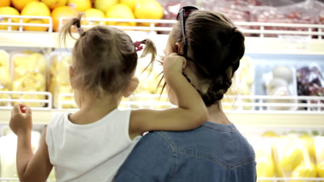 Mother with little daughter makes purchases in the supermarket Mother with little daughter makes purchases in the supermarket. Family selecting fresh fruits. grocery aisle stock videos & royalty-free footage