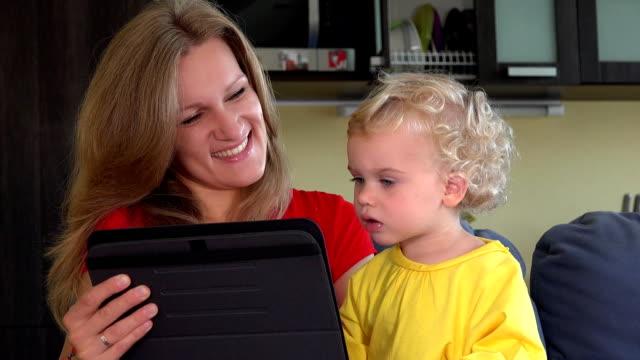 madre con hija pequeña iniciar conversación de vídeo con padre en tableta - vídeo