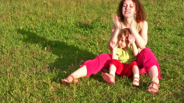 Mother with little girl on grass 2 video