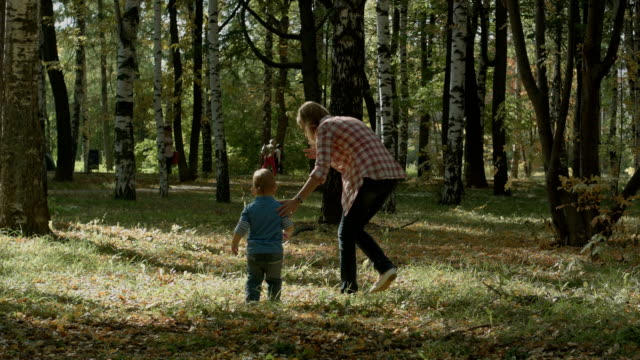 Mother with son walking outdoor in autumn video