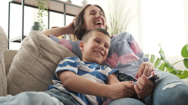 Mother with son watching comedy on tv Relaxed mother and son laughing while watching comedy on tv family watching tv stock videos & royalty-free footage