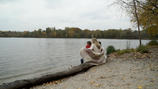 Mother with sons sits on a log near the river and family enjoys autumn view video