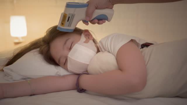 vidéos et rushes de mère avec le thermomètre vérifiant la température de la fille malade - température